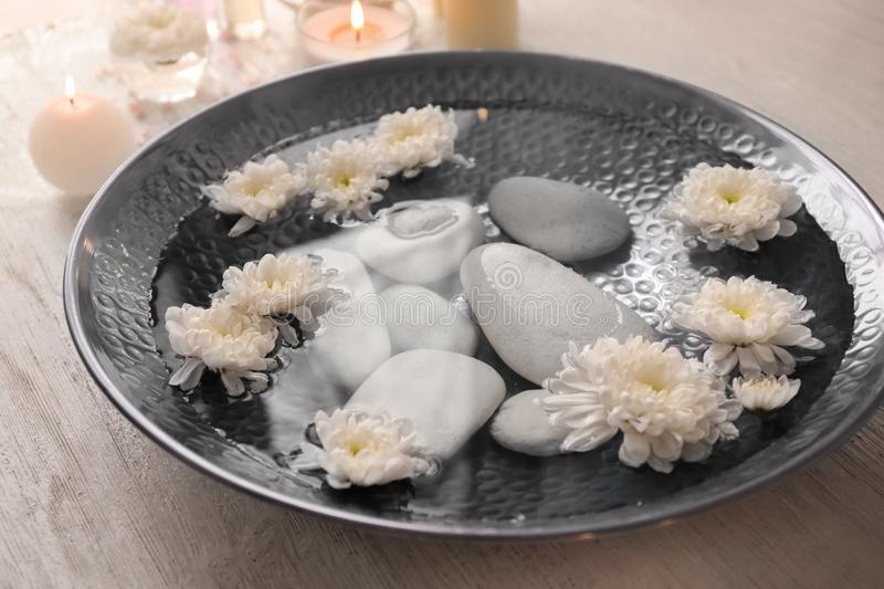Plate of water with flowers and stones prepared for pedicure treatment in spa salon royalty free stock image