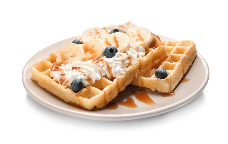 Plate with yummy waffles, whipped cream, blueberries and banana. On white background stock images