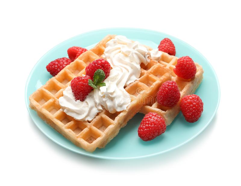 Plate with yummy waffles, whipped cream and raspberries. On white background stock photo