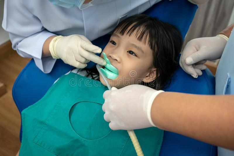 Plateau acéré de silicium de fille asiatique de fluorure et d'aspiration dentaire photographie stock libre de droits
