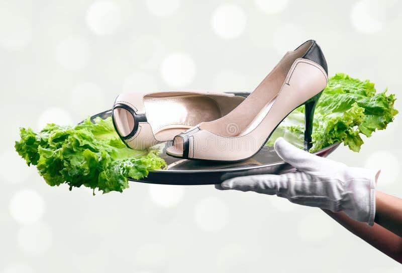 Plateau avec des paires de chaussures femelles dans des mains du serveur photographie stock