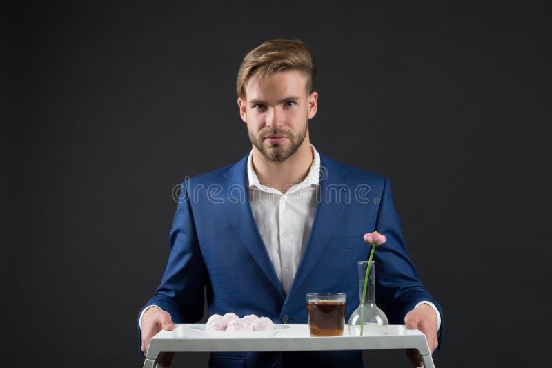 Plateau barbu de prise d'homme avec la fleur Nourriture macho et boisson de dessert de service Serveur dans le costume formel Ser image libre de droits