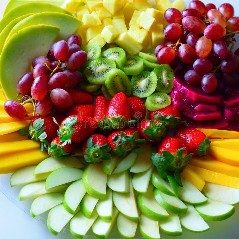 Plateau cru d'assortiment de fruits du plat blanc, sur la table blanche images libres de droits