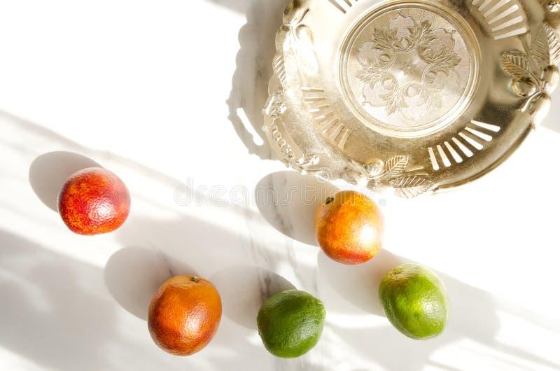 Plateau d'or rustique avec les éraflures et les oranges sanguines, chaux sur la table de marbre blanche Sun ombrage sur la la tab photographie stock