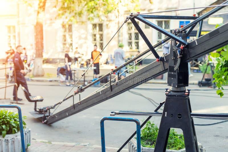 Plateau de filmagem com equipamento e a equipe profissionais da produção dos meios na rua da cidade Cinematografia exterior Guind fotografia de stock