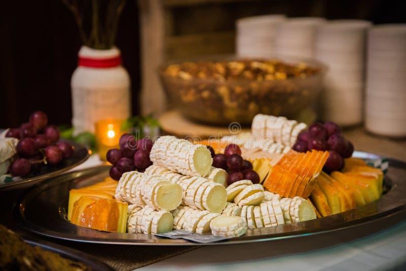 Plateau de fromage assorti avec des raisins au banquet photos libres de droits