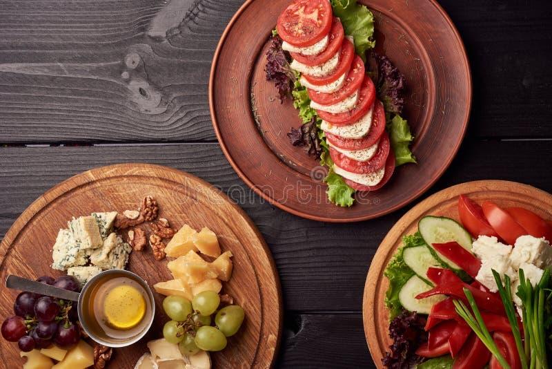 Plateau de fromage : Parmesan, cheddar, Gouda, Gorgonzola, brie et autre avec des noix, des olives et des légumes et miel dessus photo libre de droits