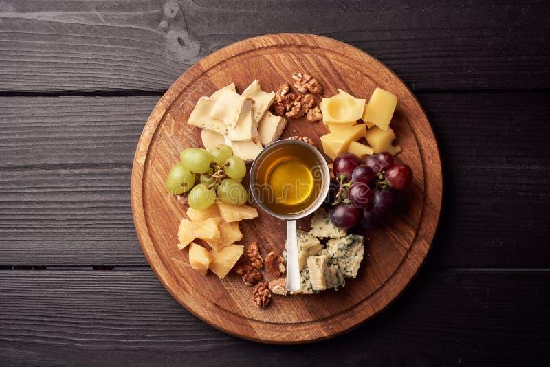 Plateau de fromage : Parmesan, cheddar, Gouda, Gorgonzola, brie et autre avec des noix, des olives et le miel sur le conseil en b images stock