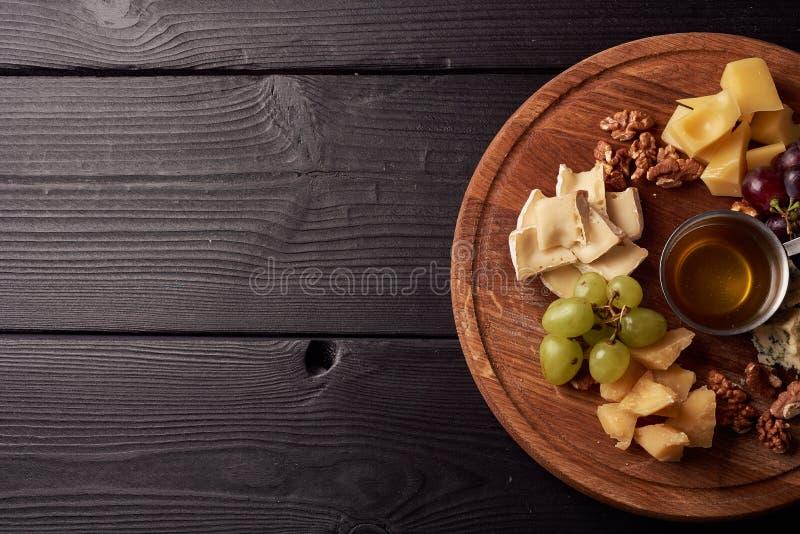 Plateau de fromage : Parmesan, cheddar, Gouda, Gorgonzola, brie et autre avec des noix, des olives et le miel sur le conseil en b images libres de droits