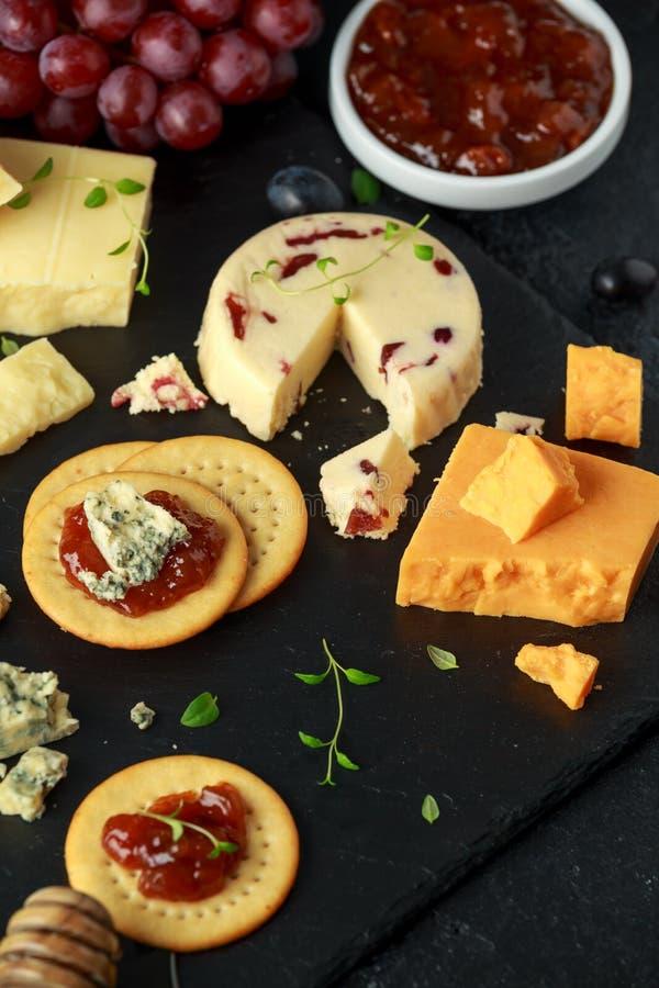 Plateau de fromage servi avec des raisins, chutney de bière anglaise, miel, biscuits sur le conseil en pierre Brie, cheddar, Leic photo stock