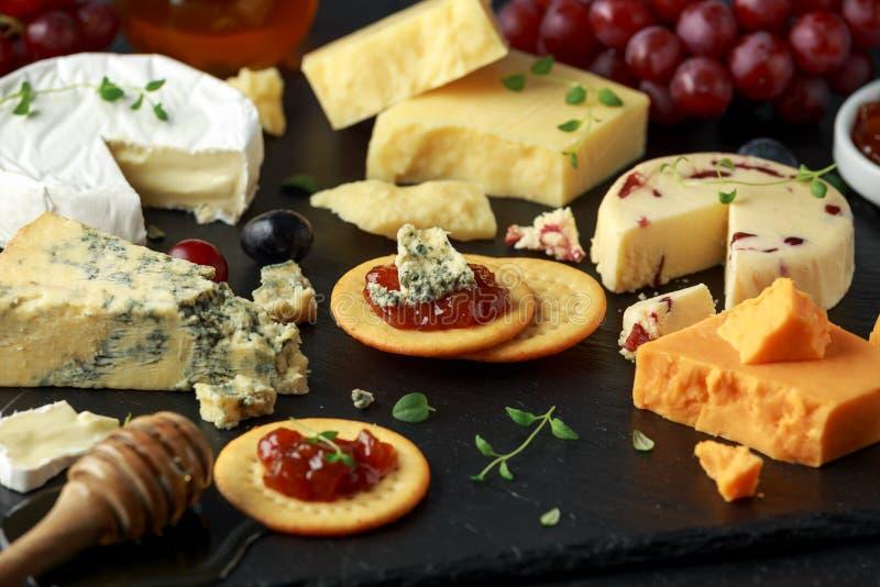 Plateau de fromage servi avec des raisins, chutney de bière anglaise, miel, biscuits sur le conseil en pierre Brie, cheddar, Leic images libres de droits