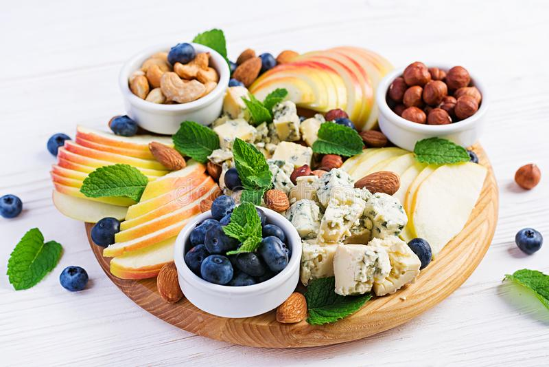 Plateau de fromages assortis, bleuets, pommes, noix sur table blanche photos stock