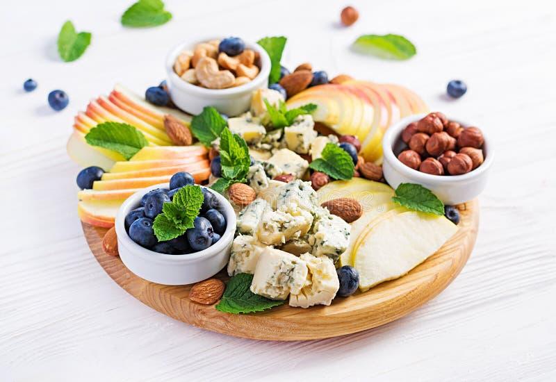 Plateau de fromages assortis, bleuets, pommes, noix sur table blanche image stock