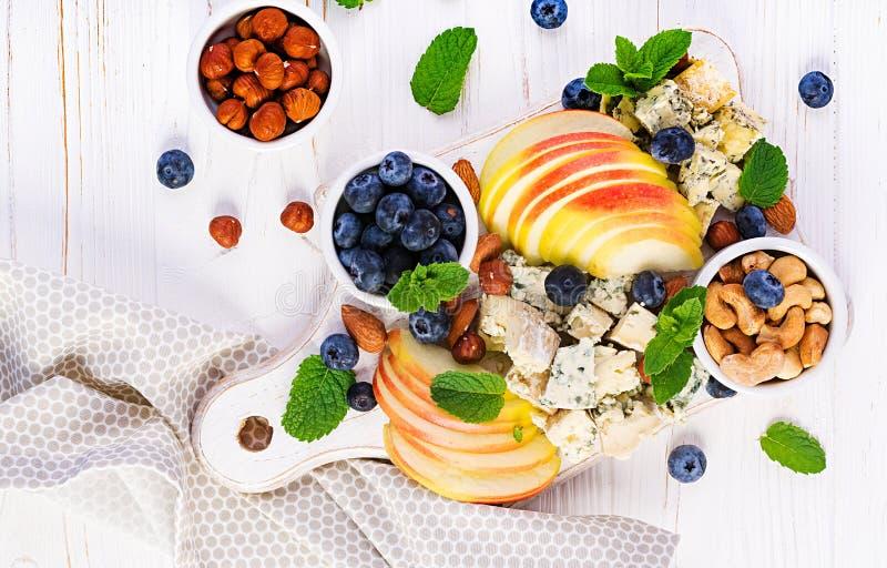 Plateau de fromages assortis, bleuets, pommes, noix sur table blanche photos libres de droits