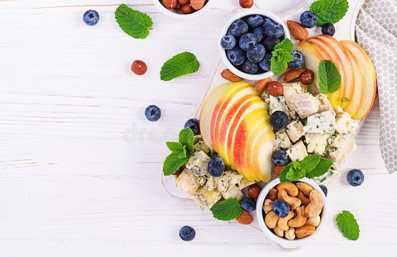 Plateau de fromages assortis, bleuets, pommes, noix sur table blanche images libres de droits