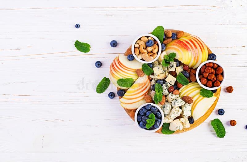 Plateau de fromages assortis, bleuets, pommes, noix sur table blanche images stock