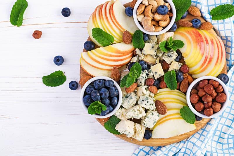 Plateau de fromages assortis, bleuets, pommes, noix sur table blanche photo libre de droits