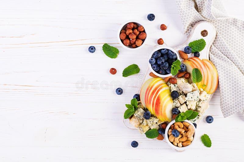 Plateau de fromages assortis, bleuets, pommes, noix sur table blanche image libre de droits