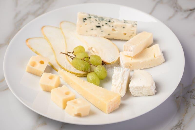 Plateau de plat de fromage avec la sélection Edamer, le parmesan, la chèvre, le bleu et le fromage fondu, le pair et les raisins  photos libres de droits