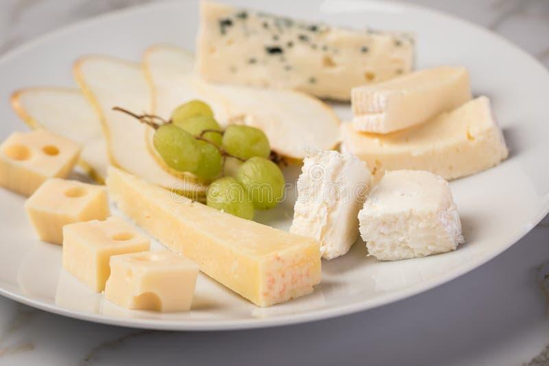 Plateau de plat de fromage avec la sélection Edamer, le parmesan, la chèvre, le bleu et le fromage fondu, le pair et les raisins  photo stock