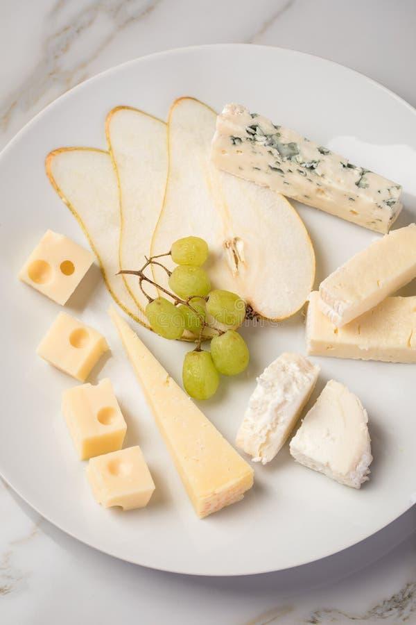 Plateau de plat de fromage avec la sélection Edamer, le parmesan, la chèvre, le bleu et le fromage fondu, le pair et les raisins  photo libre de droits
