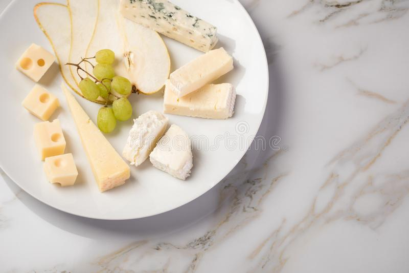Plateau de plat de fromage avec la sélection Edamer, le parmesan, la chèvre, le bleu et le fromage fondu, le pair et les raisins  image libre de droits