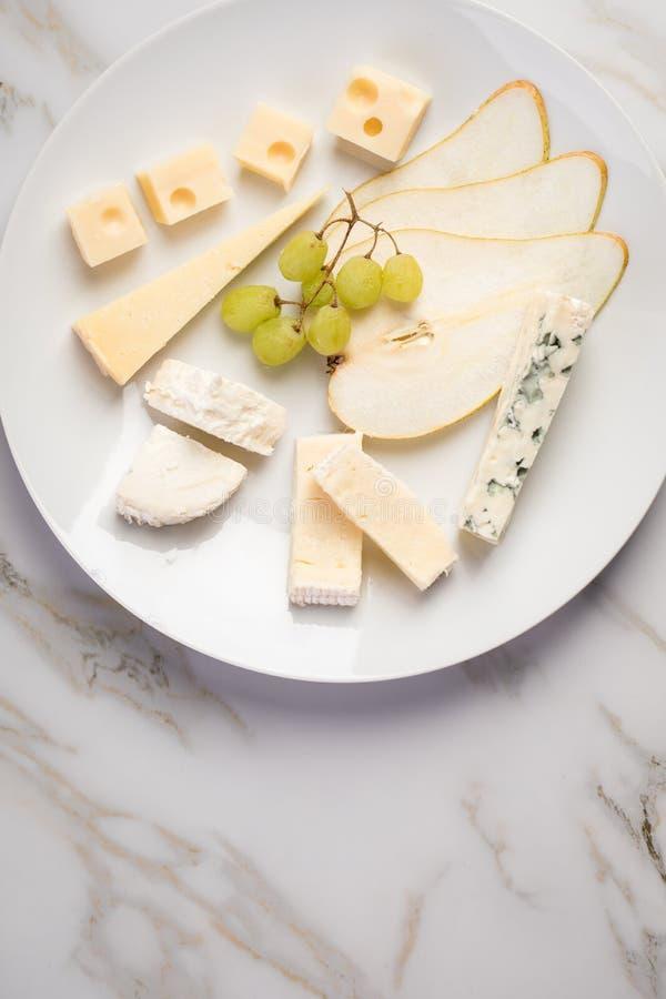Plateau de plat de fromage avec la sélection Edamer, le parmesan, la chèvre, le bleu et le fromage fondu, le pair et les raisins  photos stock