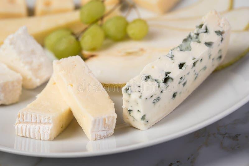 Plateau de plat de fromage avec la sélection Edamer, le parmesan, la chèvre, le bleu et le fromage fondu, le pair et les raisins  photographie stock libre de droits