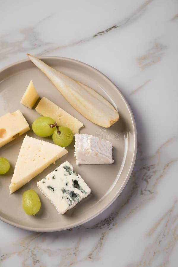 Plateau de plat de fromage avec la sélection Edamer, le parmesan, la chèvre, le bleu et le fromage fondu, le pair et les raisins  images libres de droits