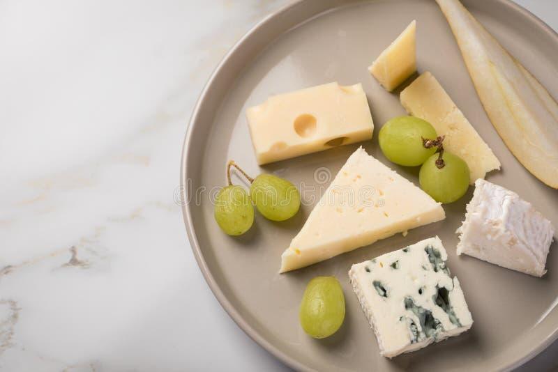 Plateau de plat de fromage avec la sélection Edamer, le parmesan, la chèvre, le bleu et le fromage fondu, le pair et les raisins  photographie stock