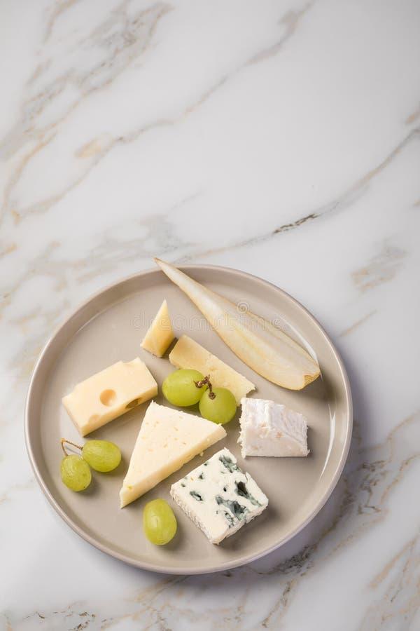 Plateau de plat de fromage avec la sélection Edamer, le parmesan, la chèvre, le bleu et le fromage fondu, le pair et les raisins  images stock