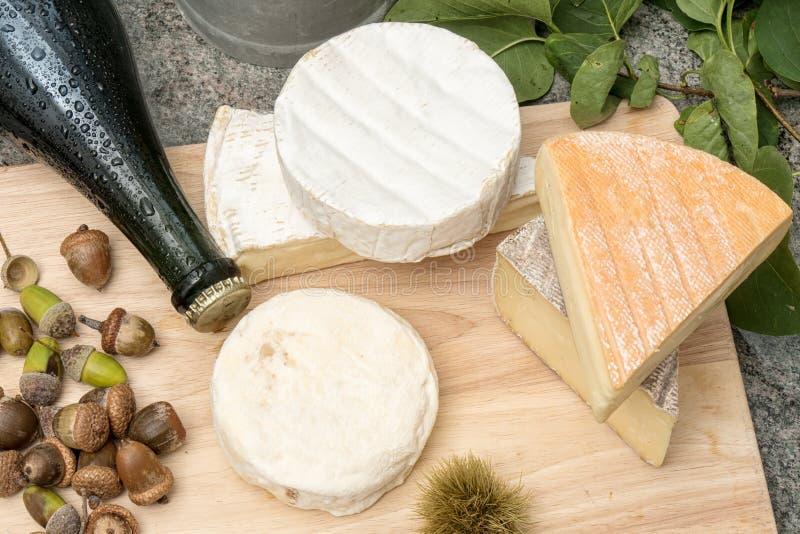 Plateau en bois avec des fromages et le cidre français différents photos stock