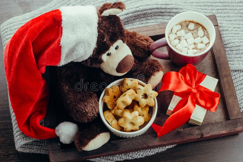 plateau en bois avec l'ours de nounours en Santa Claus, boîte-cadeau, boisson de chauffage et pain d'épice, vacances d'hiver conf photos stock