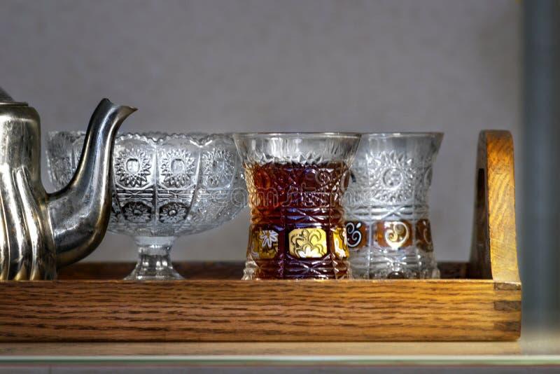 Plateau en bois avec une théière et un verre cristal avec le thé photos stock