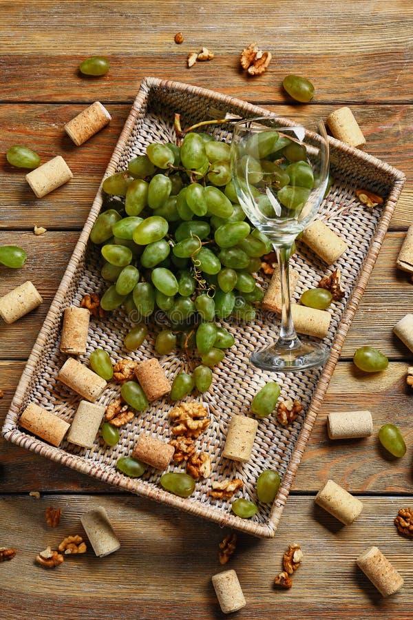 Plateau en osier avec des raisins et le verre à vin mûrs sur la table en bois photos libres de droits