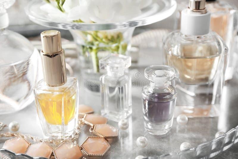Plateau en verre avec les bouteilles et le collier de parfum, photographie stock