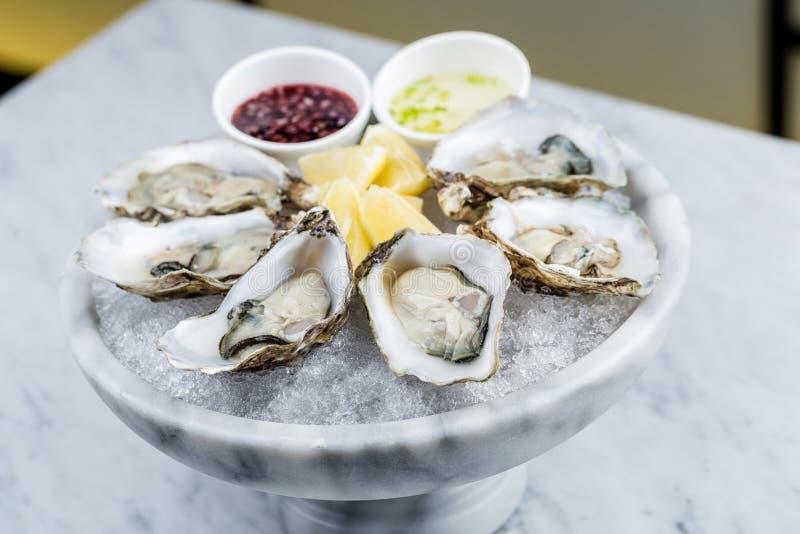 Plateau frais d'huîtres avec de la sauce et le citron photos libres de droits