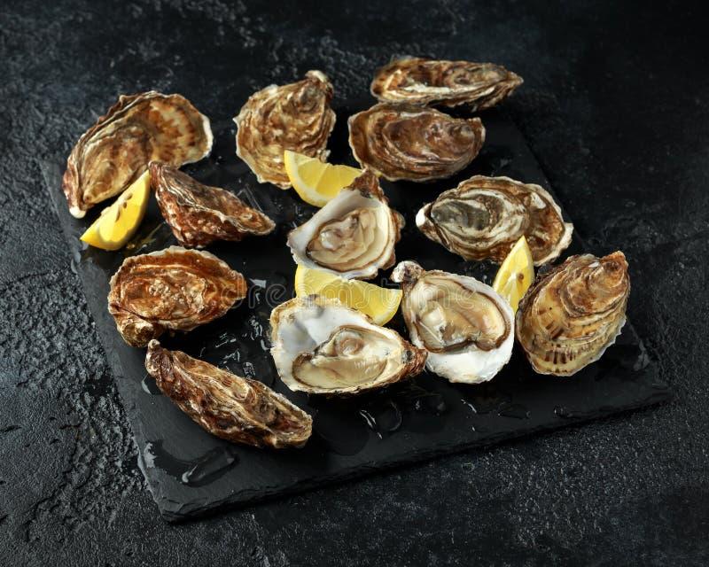 Plateau frais d'huîtres avec le citron et la glace prêt à s'ouvrir et manger photographie stock