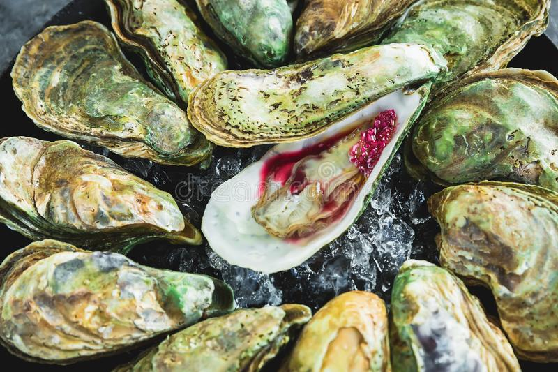 Plateau frais d'huîtres de mer avec de la sauce et la glace Fruits de mer de luxe photo stock