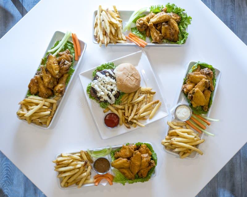 Plateaux des ailes de poulet, des cheeseburgers, et des pommes frites image stock