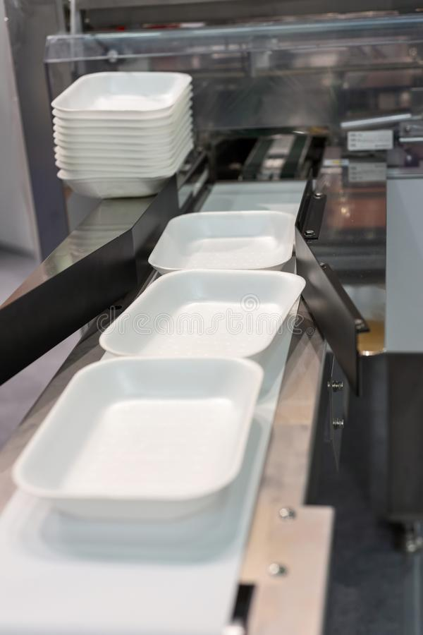 Plateaux en plastique de nourriture sur le convoyeur de la machine de conditionnement photographie stock