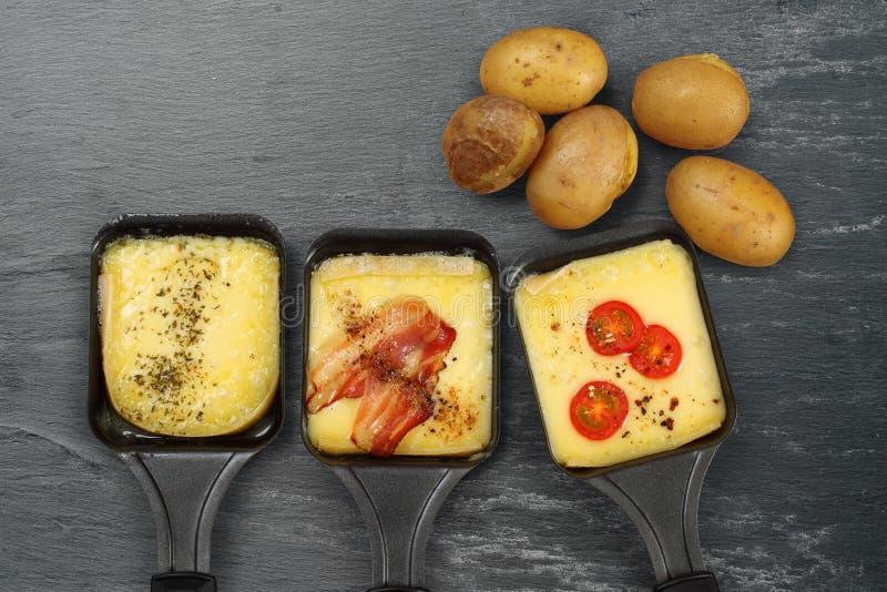 Plateaux et pommes de terre de Raclette image stock