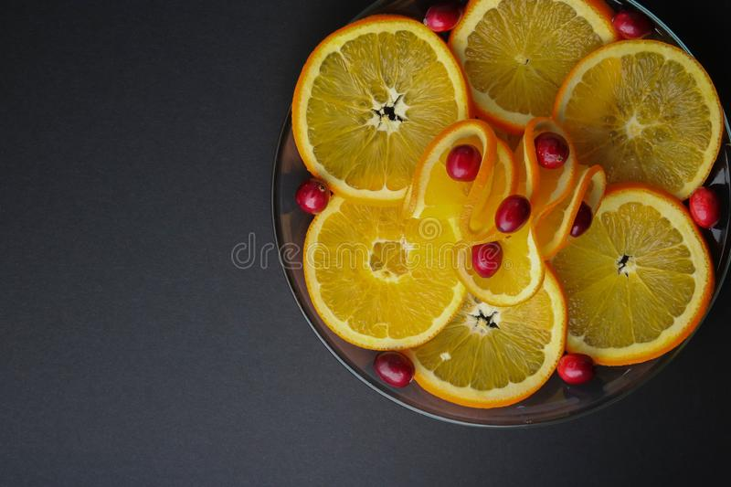 Plated cranberries and juicy orange slices royalty free stock photography