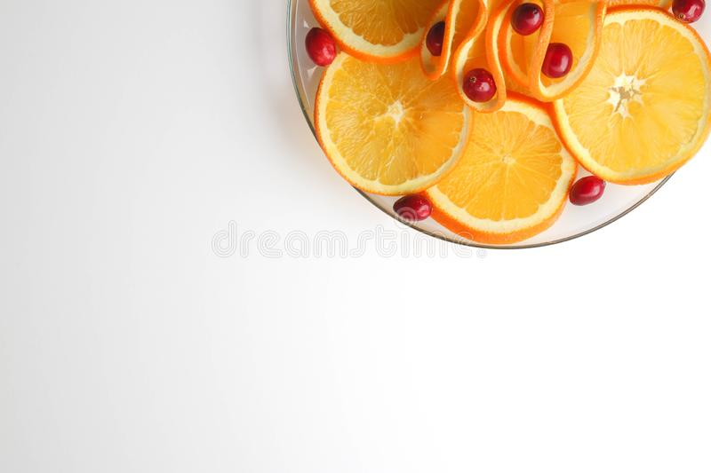 Plated cranberries and juicy orange slices royalty free stock photo