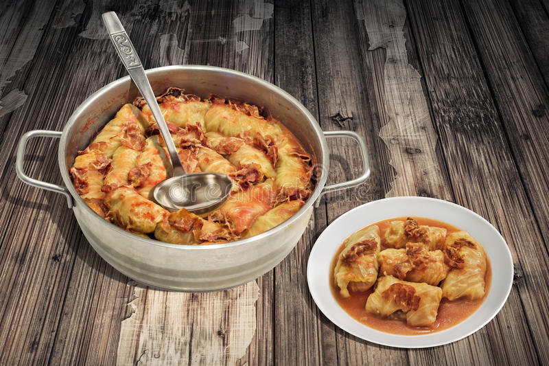 Plateful Of Pickled Cabbage Rolls Stuffed With Minced Meat Cooked In Steel Saucepot Served On Old Cracked Flaky Garden Table stock images