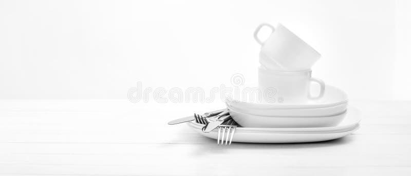 Platen, koppen en zilveren bestek op lichte witte achtergrond stock foto's