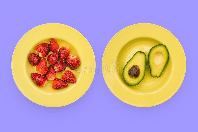 Platen met gezonde vruchten op een heldere achtergrond Gele plaat met aardbeien en avocado Het fruit en de aardbeien van de besno stock afbeeldingen