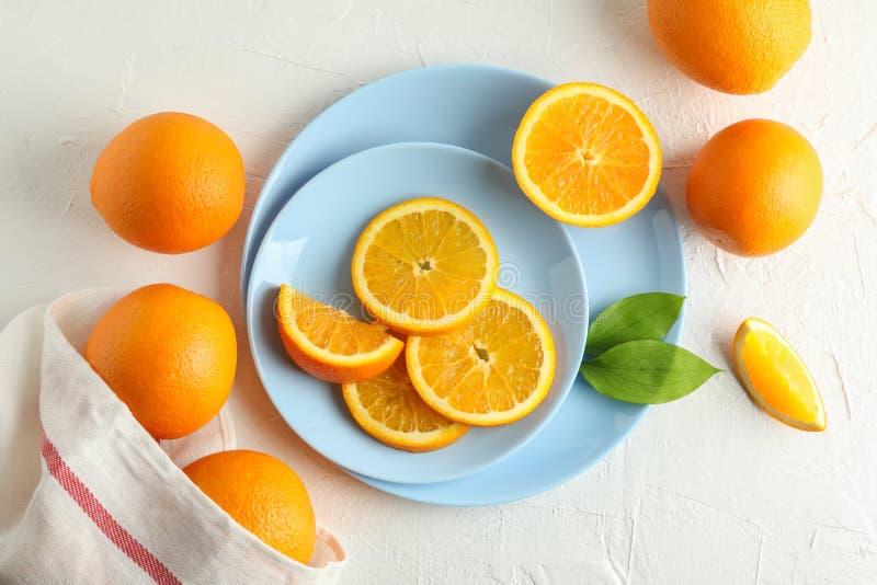 Platen met oranje plakken en keukenhanddoek op witte achtergrond royalty-vrije stock foto