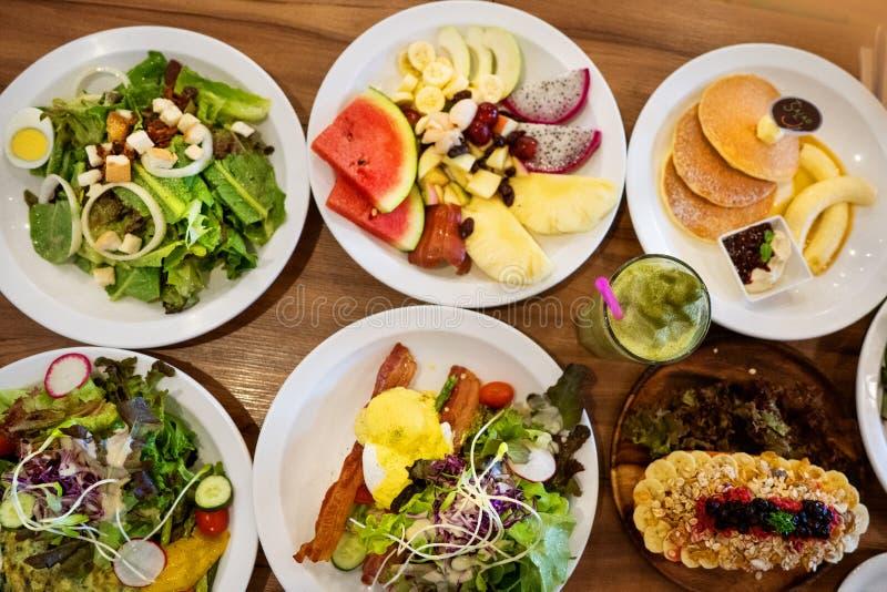 Platen met schotels tribune op staal, salades, desserts en vruchten royalty-vrije stock afbeelding