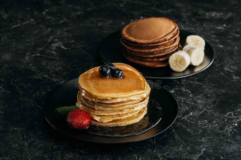 platen met stapels smakelijke pannekoeken met vruchten stock fotografie